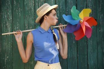 Schön geschminkt macht das Leben gleich noch mehr Spaß. Bunt gekleidete Frau mit kleinem Windrad-Spielzeug.